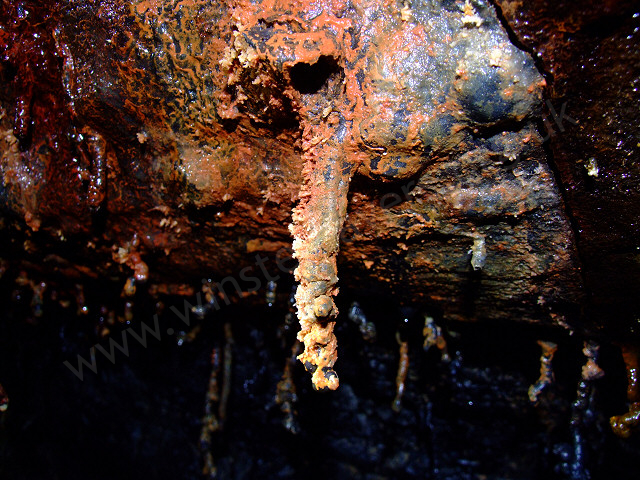 A lava tube formation, encrusted in mineral deposits.